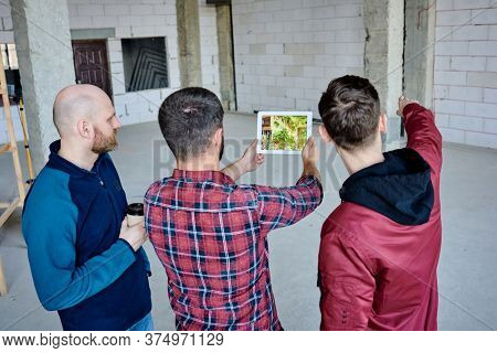 Young designer of interior holding touchpad with photo of green plant on its screen while his colleague pointing at unfinished brick wall