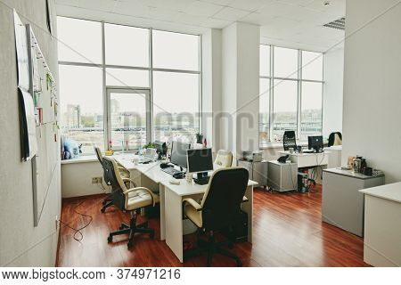 Interior of contemporary large office in modern center with desks, computer monitors, white leather armchairs and other stuff