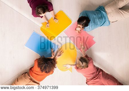 Top view of several young women and man lying on the floor with paper speech bubbles and discussing what to write on them