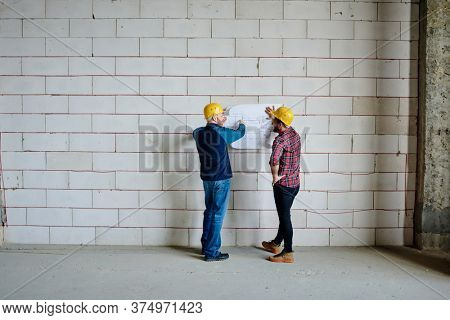 Two professional engineers in hardhats standing by brick wall and discussing sketch of unfinished building at working meeting
