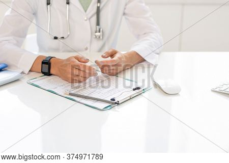 Hands of young female clinician in whitecoat sitting by desk and consulting someone while reading information in medical document