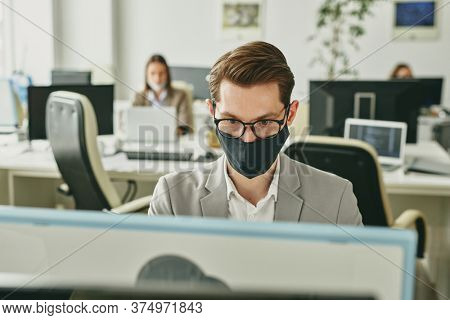 Contemporary young businessman in eyeglasses and protective black textile mask looking at computer screen while working in office