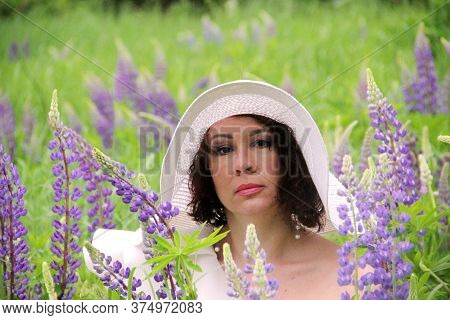 Enchanting Brunette In A White Hat In A Field Of Blooming Lupines, Portrait In Warm Colors, Close-up