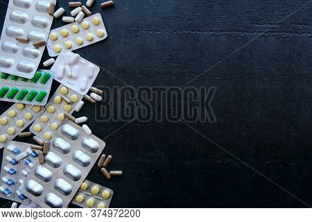 Medicine Green And Yellow Pills Or Capsules On Black Background With Copy Space. Drug Prescription F