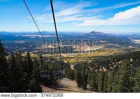 Riding A Chair Lift Over The Changing Autumn Colors Of A Mountain Forest.
