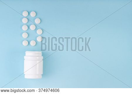 Vitamin B Pills Dropped From Bottle On Blue. Letter B Inscription From Tablets. Vitamin B12 Concept.