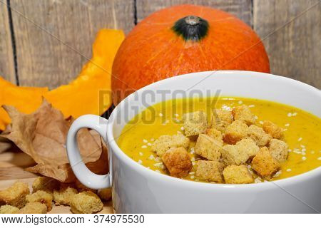 Autumn Pumpkin Soup With Sesame Seeds On A Wooden Background. Pumpkin Puree Soup With Crackers And S