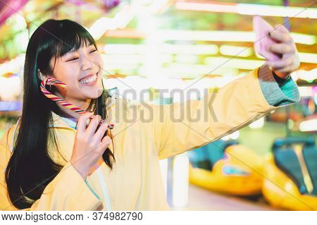 Asian Girl Taking Selfie With Mobile Phone In Amusement Park - Happy Woman Having Fun With New Trend
