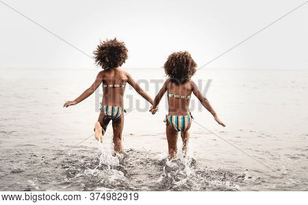 Happy Sisters Running Inside Water During Summer Time - Afro Kids Having Fun Playing On The Beach -