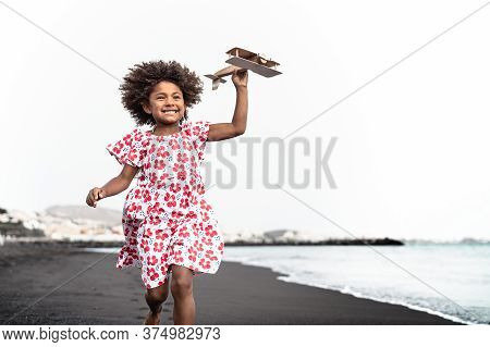 Afro Child Playing With Wood Toy Airplane On The Beach - Little Kid Having Fun During Summer Holiday