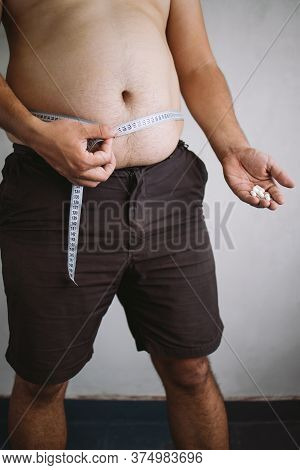 Weight Loss, Diet, Healthy Lifestyle. Overweight Man Measuring His Waistline With Tape And Taking Di