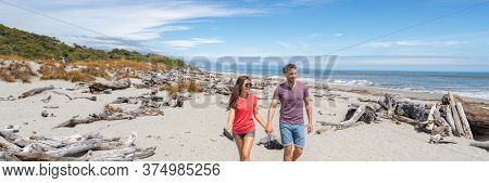 Panoramic banner of Couple walking on beach in New Zealand - people in Ship Creek on West Coast of New Zealand. Tourist couple sightseeing tramping on South Island of New Zealand.