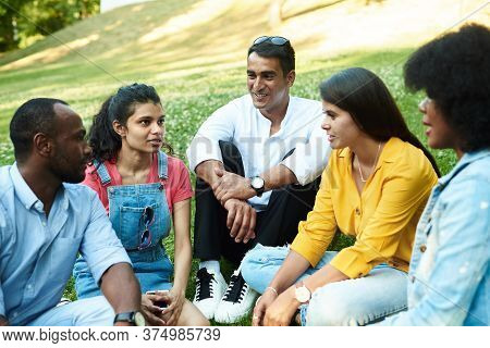 Afghan, Black, Mexican And Indian Chatting While Sitting In The Park On The Grass. The Concept Of Co