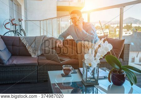 Stay at home, working in house. Man spend free time on terrace in home clothes, working hours. Work with laptop and drinking tea. Beautiful views in sunny day. Home Office.