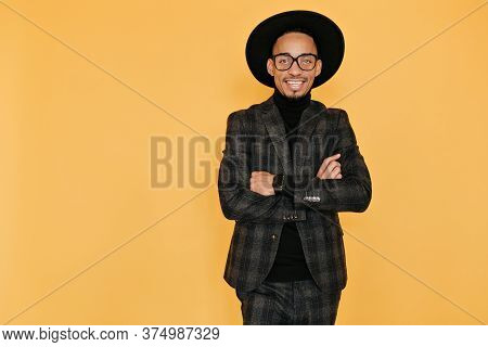 Studio Shot Of Smiling African Guy With Inspired Face Expression. Indoor Photo Of Pleased Black Man