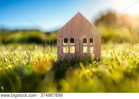 Green ecological house in empty field at sunset concept for construction and real estate