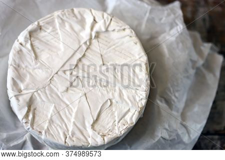 Round Camembert Cheese In Paper. Camembert Cheese