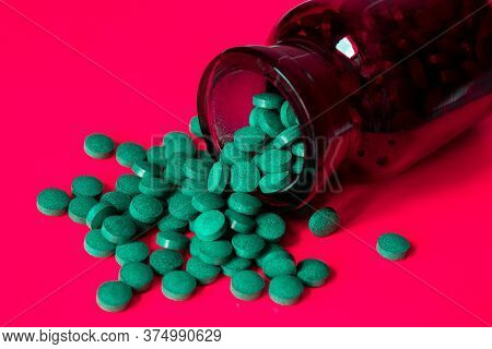 Tablets With Arthrospore Or Spirulina Poured Out Of A Dark Glass Bottle On A Red Background