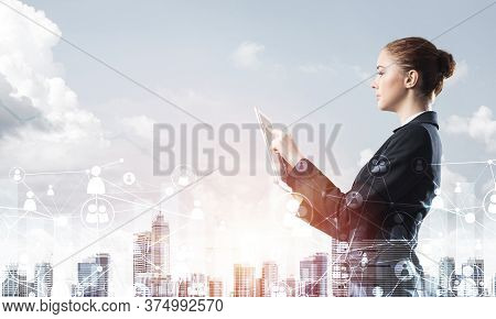 Young Businesswoman With Tablet Computer On Modern Cityscape Background. Double Exposure Concept Wit