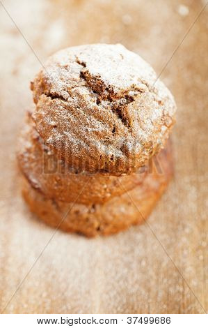 soft ginger cookies three stacked and dusted on wooden table, sieve with caster sugar on background, shallow dof poster