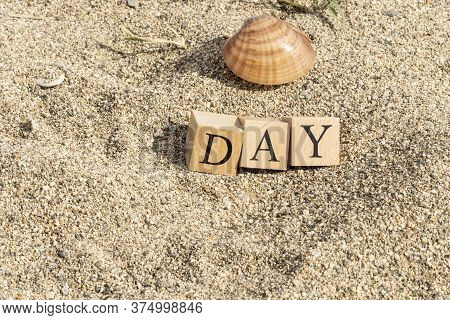 Day Word Made Of Wooden Cubes. Close-up On The Beach Sand.