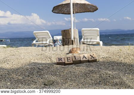 The Word Relax From Wooden Cubes. Close-up On The Beach Sand.