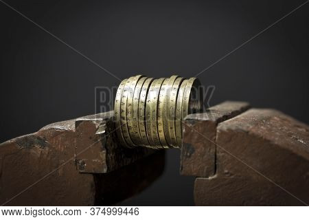A Few Coins In A Metal Vise. Concept Of Economic Problems
