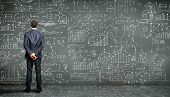 Business person standing against the blackboard with a lot of data written on it poster