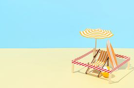 Deck Chair With Umbrella, Surfboard And Ball On The Beach. Isolated Vacation Spot At Resort. Minimal