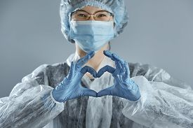 Young Woman In Glasses With A Medical Mask And Hands In Latex Glove Shows The Symbol Of The Heart.