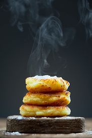 Hot Pancakes On A Wooden Plate Sprinkled With Powdered Sugar On A Dark Background. Steam Rises From