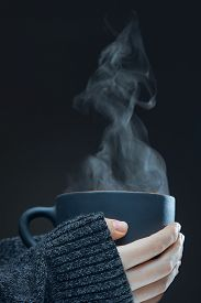 Female Hands With A Hot Cup Of Tea On A Dark Background. Steam Rises From Hot Drink.