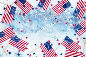 Small American Flags And Star Confetti On Ice Rink Background With Copy Space. Congratulations To Am