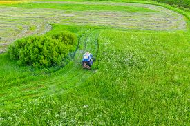 Aerial Top View Farm Scene Agricultural Tractor Mows Grass With A Mower In The Farm Fields, Haymakin