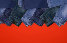 Jeanjeans Folded On Red Background, Top View With Copy Work Space.s Folded On Red Background, Top Vi