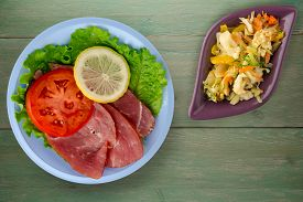 Ham With Salad, Tomato And Lemon On Light Blue Plate. Ham On Green Wooden Background .ham Wth Vegeta