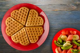 Belgian Waffles With Fruits Blue On Wooden Background. Waffles On A Red Plate Top View