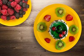 Dessert Cake With Kiwi And Strawberries On A Brown Wooden Background. Festive Dessert On A Yellow Pl