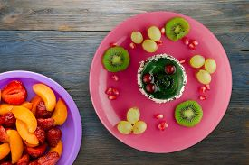 Dessert Of Cake And Fruit Grapes, Kiwi, Pomegranate On A Blue Wooden Background. Dessert On A Pink P