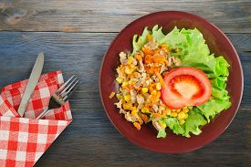 Salad With Chicken Stomachs With Carrots And Corn And Salad On Brown Plate With Fork And Knife Top V