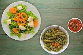 Salad Of Cheese, Lettuce, Corn, Pepper On A Green Wooden Background. Vegetarian Salad On A White Pla