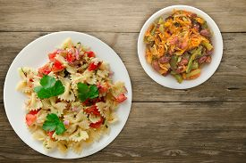 Pasta On A White Plate. Pasta Tomatoes, Onions, Cabbage On A Wooden Background. Pasta With Vegetario
