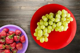 Grapes On A Black Wooden Background. Grapes On A Red Plate.healthy Vegetarian Food