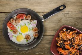 Fried Eggs With Sausage In A Frying Pan On Brown Wooden Background.fried Eggs With Vegetable Salad T