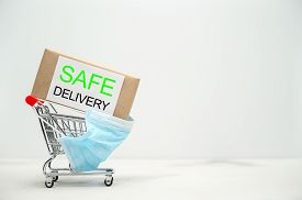 Safe Home Delivery. Shopping Cart With A Parcel On A Light Table. Online Shopping, Stay Home.