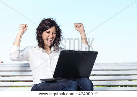 Euphoric Businesswoman With A Laptop Sitting On A Bench