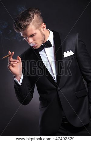 elegant young fashion man in tuxedo taking a smoke and holding a hand in his pocket while looking away form the camera. on black background