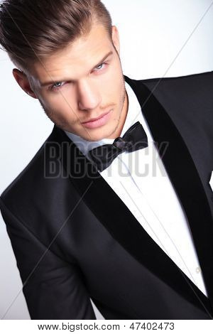 closeup cutout picture of an elegant young fashion man in tuxedo looking at the camera.on gray background