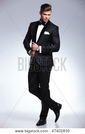 full length portrait of an elegant young fashion man in tuxedo looking at the camera while holding his hands on his jacket and a leg behind the other. on gray background