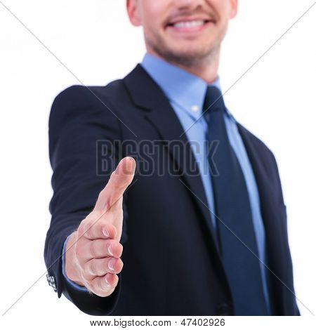 closeup on a young business man offering a hand shake with a smile on his face. focus on the hand. on white background